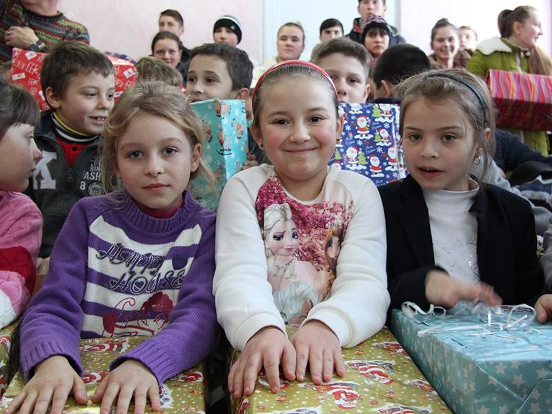 Glückliche Kinder mit Weihnachtspäckchen in Otac an der Grenze zur Ukraine